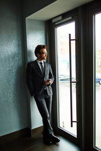 Businessman in suit standing by the door and looking through it