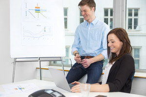 Businessman Smiling By Flipchart While Female Colleague Using La