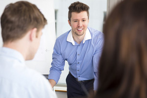 Businessman Smiling While Looking At Colleagues In Office