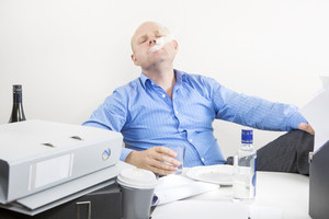 Businessman smokes and drinks at the office