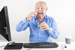 Businessman taking pills for headache