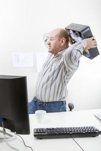 Businessman Throwing Computer Chassis By Desk