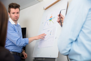 Businessman Touching Document On Flipchart While Giving Presenta
