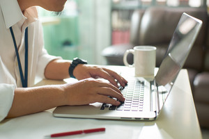 Businessman using laptop with tablet and pen on white table in office with a cup of coffee,side view and selected focus.