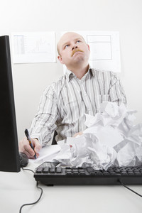 Businessman Writing With Rejected Papers On Keyboard