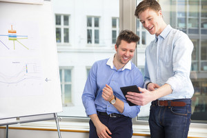 Businessmen Using Digital Tablet At Window Sill