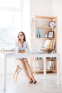 Businesswoman sitting in her office and using laptop while talking by phone