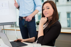 Businesswoman Using Laptop While Colleague Giving Presentation