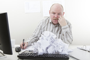 Busy and overworked office worker with a heap of paper at the office desk. To much work.
