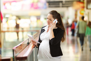 Busy pregnant woman talking on the phone in shopping centre
