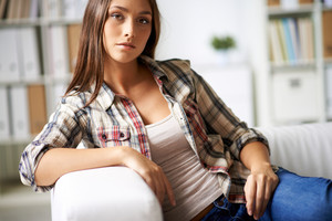 Calm girl in casual clothes looking at camera inside