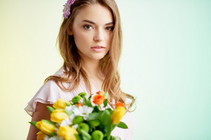 Calm girl with tulips and daisies looking at camera
