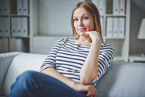 Calm woman in casual clothes looking at camera inside