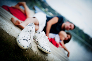 Canvas shoes detail, family with baby boy sitting on pier on the background