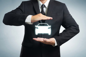 Car (automobile) insurance and collision damage waiver concepts. Businessman with protective gesture and icon of car. Wide banner composition and bokeh in background.