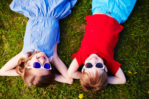 Carefree children in sunglasses relaxing in green grass