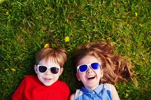 Carefree friends in sunglasses lying on green grass