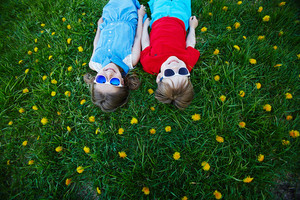 Carefree friends in sunglasses lying on green lawn with dandelions