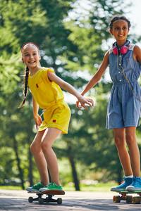 Carefree girls on skateboards spending summer weekend in park