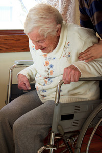 Caregiver helping senior lady get up from wheelchair