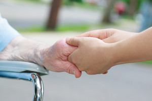 Caregiver holding an elderly womans hand outside