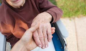 Caregiver holding seniors hand in wheelchair