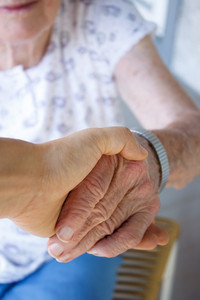 Caregiver holding seniors hand on porch