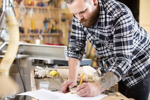 Carpenter plans work and take notes at project drawing