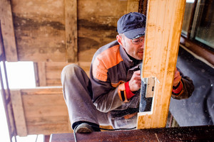 Carpenter with grinder. Man grinding planks of wood for home construction.