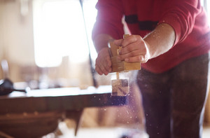 Carpenter working with planer on wooden plank in workshop