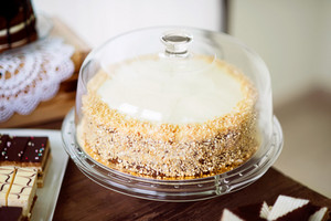 Carrot cake with nuts and glaze on glass cake stand. Candy bar with various cakes. Studio shot.