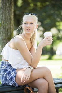 Casual girl sits on a bench and drinks coffee