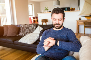 Casual hipster man working from home using smart watch, sitting in living room