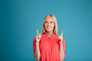 Casual inspired young woman in red dress pointing two fingers up isolated on a blue background