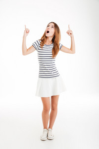 Casual inspired young woman pointing two fingers up over white background