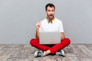Casual man with headphones sitting on the floor with laptop and pointing finger up over gray background