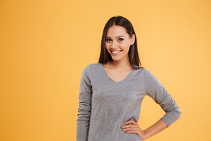Casual model in studio with arm at hip. smiling girl looking at camera
