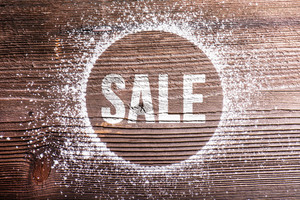 Chalk sale sign. Studio shot on wooden background.