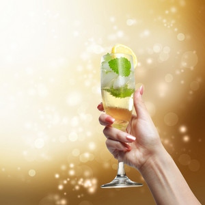 Champagne glass being lifted up in the air by a young woman on golden shinning background