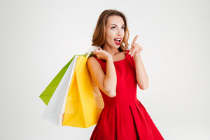Charming attractive woman in red dress holding shopping bags and pointing finger away isolated on a white background