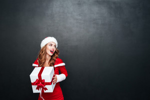 Charming brunette woman in red santa claus outfit holding big xmas present isolated on the black background
