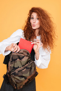 Charming plauful curly young woman putting book into backpack