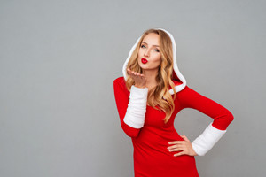 Charming playful young woman in new year costume standing and sending a kiss over grey background