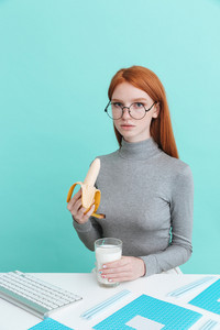 Charming young woman in glasses drinking milk and eating banana at the table over blue background