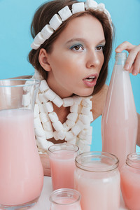 Charming young woman in marshmallow necklace sitting at the table with pink beverage over blue background