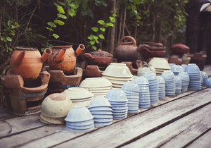 Cheap ceramic cups, plates and bowls basket on a street market for sale in Vietnam
