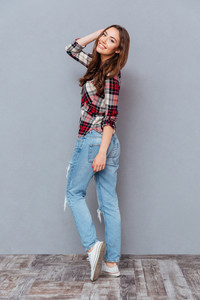 Cheeerful beautiful young woman in plaid shirt and jeans smiling and posing