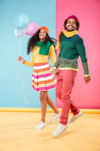 Cheerful african american young couple in hats and scarves with balloons walking and jumping