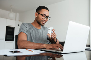 Cheerful african man dressed in grey t-shirt and wearing eyeglasses drinking water while using laptop.
