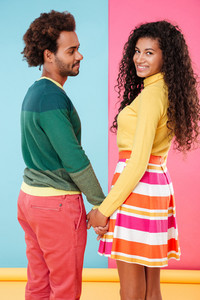 Cheerful african young couple smiling and holding hands over colorful background